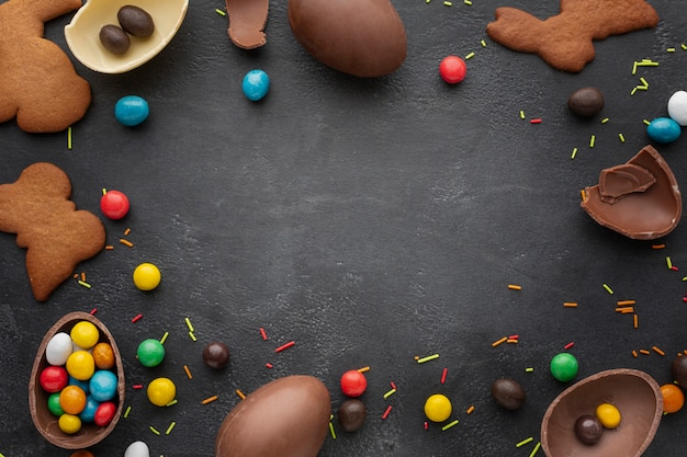 Top view of chocolate easter eggs with candy and cookies frame