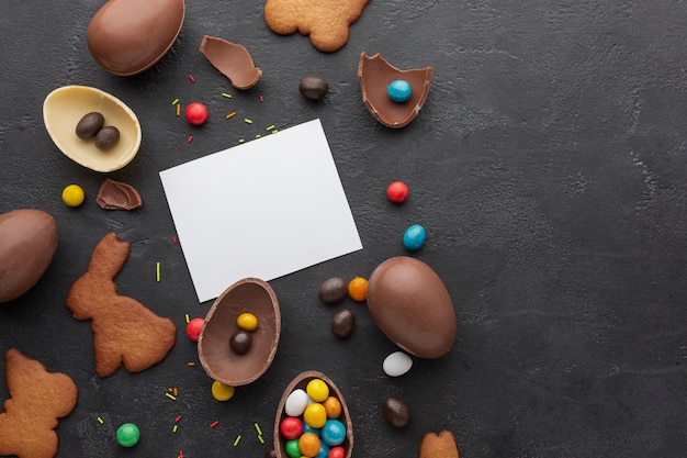 Top view of chocolate easter eggs with colorful candy and copy space