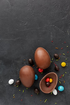 Top view of chocolate easter eggs with colorful candy inside and copy space