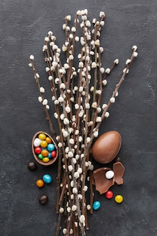 Top view of chocolate easter eggs with colorful candy inside and flowers