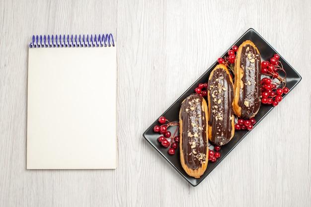 Вид сверху шоколадные эклеры и смородина на черной изометрической прямоугольной тарелке с правой стороны и блокнот с левой стороны белой деревянной земли