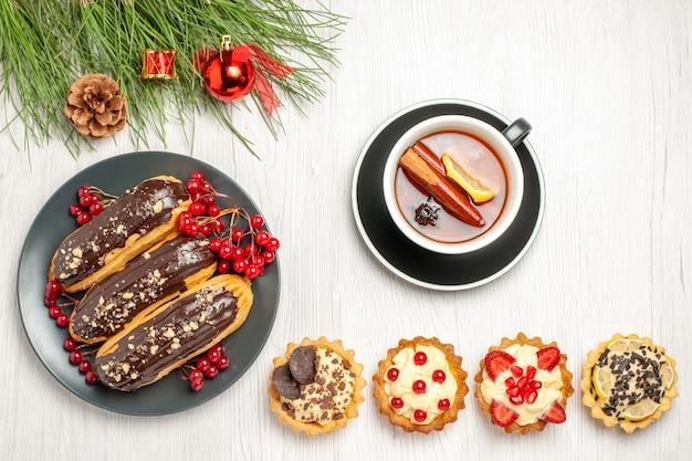 Вид сверху шоколадные эклеры и смородина на серой тарелке чашка лимонных пирожных чая с корицей и сосновые листья с рождественскими игрушками на белой деревянной земле