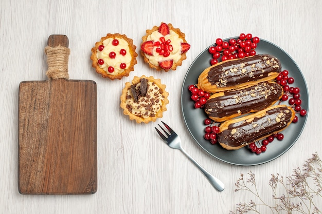 灰色のプレートのトップビューチョコレートエクレアとスグリは、白い木製のテーブルの上にフォークとまな板をクッキーします