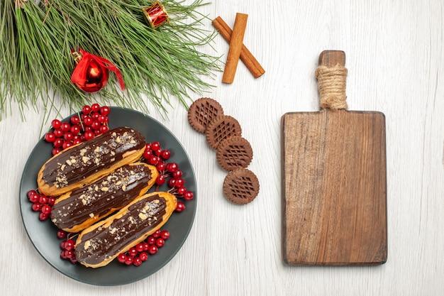 Вид сверху шоколадные эклеры и смородина на серой тарелке, печенье, скрещенные с корицей и сосновыми листьями с рождественскими игрушками и разделочной доской на белом деревянном столе