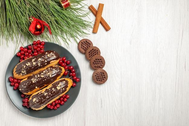Вид сверху шоколадные эклеры и смородина на серой тарелке, печенье, скрещенные с корицей и сосновыми листьями с рождественскими игрушками на белом деревянном столе