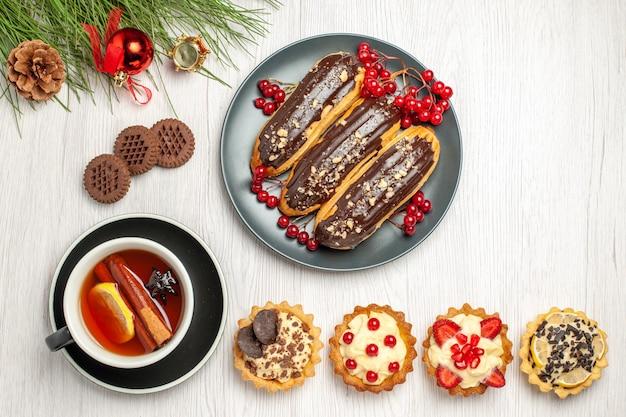 Вид сверху шоколадные эклеры и смородина на серой тарелке, пироги с лимоном и корицей, печенье и листья сосны с рождественскими игрушками на белой деревянной земле
