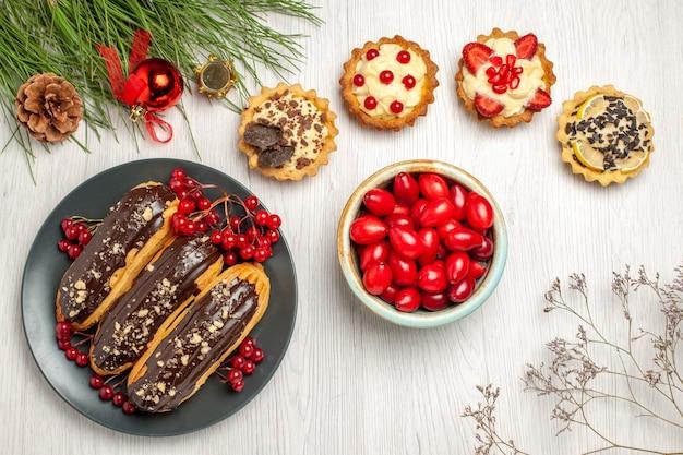 Вид сверху шоколадные эклеры и смородина на серой тарелке, пироги с кизилом и сосновыми листьями с рождественскими игрушками на