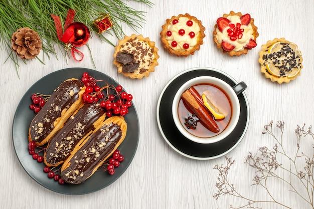 Вид сверху шоколадные эклеры и смородина на серой тарелке пироги чай с лимоном и корицей и листья сосны с рождественскими игрушками на белом деревянном столе