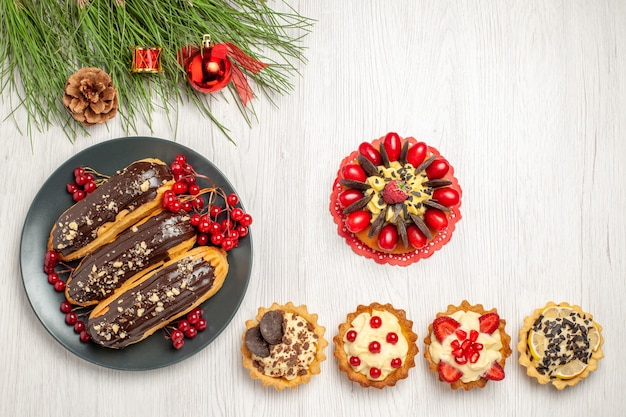 Top view chocolate eclairs and currants on the grey plate berry cake tarts at the bottom and pine tree leaves with christmas toys on the white wooden ground with copy space