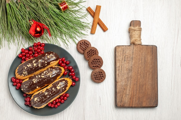 Top view chocolate eclairs and currants on the grey plate cookies crossed cinnamons and pine tree leaves with christmas toys and a chopping board on the white wooden table