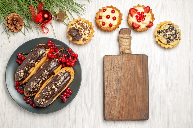 Top view chocolate eclairs and currants on the grey plate tarts a chopping board and pine tree leaves with christmas toys on the white wooden ground
