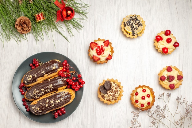 Top view chocolate eclairs and currants on the grey plate tarts and pine tree leaves with christmas toys on the white wooden ground