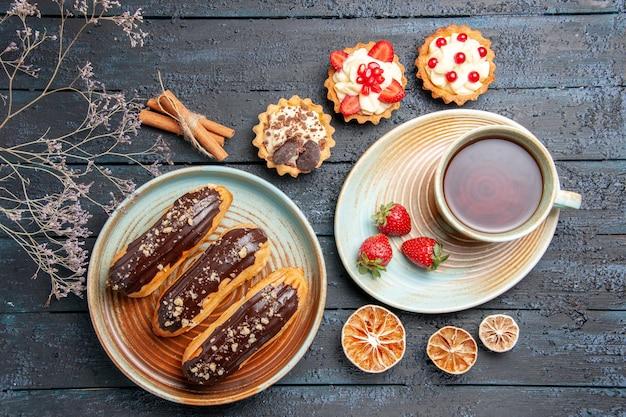 Вид сверху шоколадные эклеры на овальной тарелке, чашка чая и клубника на блюдце, пироги с корицей и сушеными лимонами на темном деревянном столе