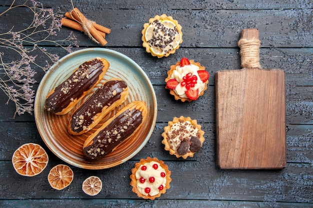 乾燥したレモンのタルトとシナモンに囲まれた楕円形のプレート上のトップビューチョコレートエクレアと暗い木製のテーブルのまな板