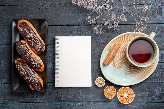 Вид сверху шоколадные эклеры на прямоугольной тарелке, блокнот и чашка чая с сушеными лимонами и корицей на темном деревянном столе
