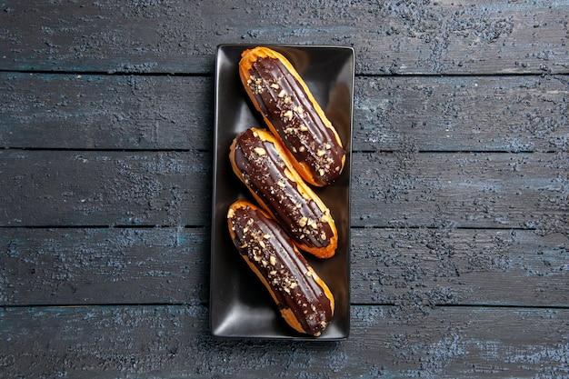 空きスペースのある暗い木製のテーブルの中央にある長方形のプレート上の上面図チョコレートエクレア