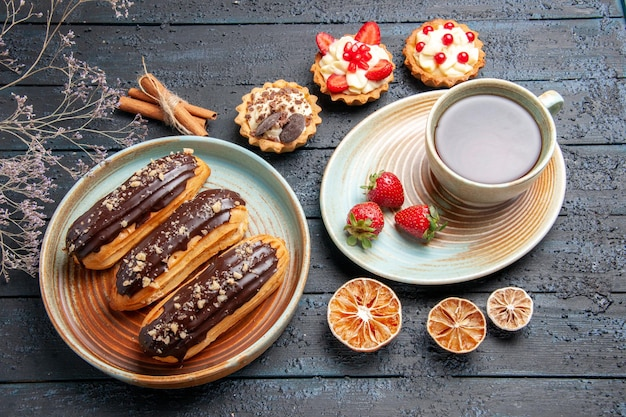 Top view chocolate eclairs on oval plate a cup o tea and strawberries on saucer tarts cinnamon and dried lemons on the dark wooden ground