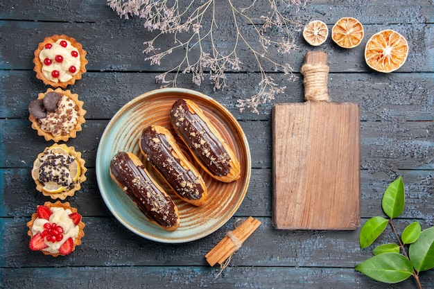 Top view chocolate eclairs on oval plate dried flower branch cinnamon dried oranges leaves a chopping board and vertical row tarts on the dark wooden table