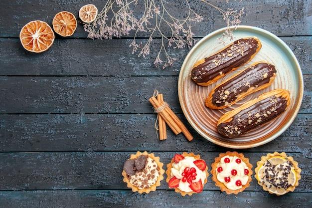 Vista dall'alto eclairs al cioccolato sulla piastra ovale crostate arance essiccate alla cannella sul tavolo di legno scuro con spazio di copia