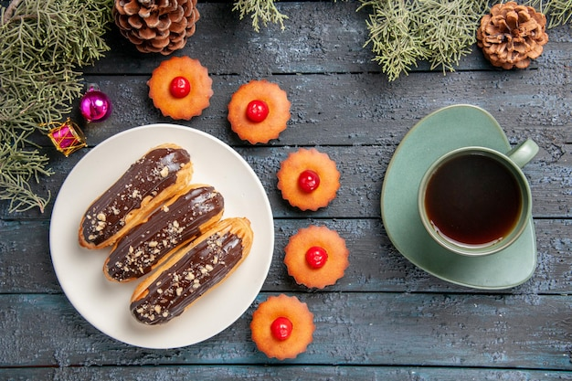Vista dall'alto bignè al cioccolato su piastra ovale bianca rami di abete giocattoli di natale cupcakes e una tazza di tè sul tavolo di legno scuro