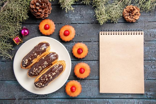 Vista dall'alto eclairs al cioccolato su piastra ovale bianca rami di abete giocattoli di natale cupcakes e un taccuino sulla tavola di legno scuro