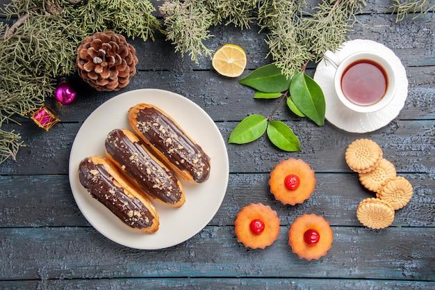 Vista dall'alto bignè al cioccolato su piastra ovale bianca rami di abete giocattoli di natale fetta di limone una tazza di biscotti da tè e cupcakes sul tavolo di legno scuro