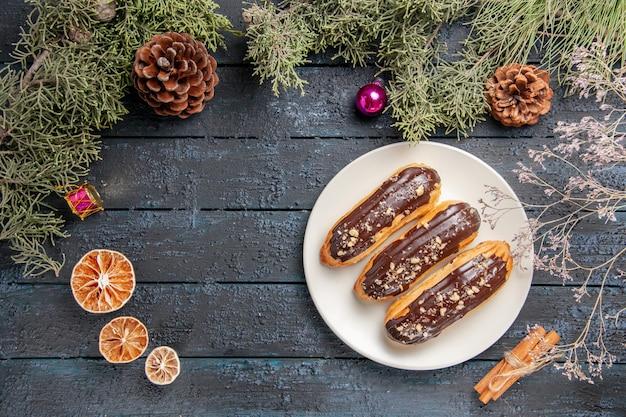 Vista dall'alto bignè al cioccolato su piastra ovale bianca rami di abete e coni giocattoli di natale arance secche cannella sul tavolo di legno scuro con spazio libero