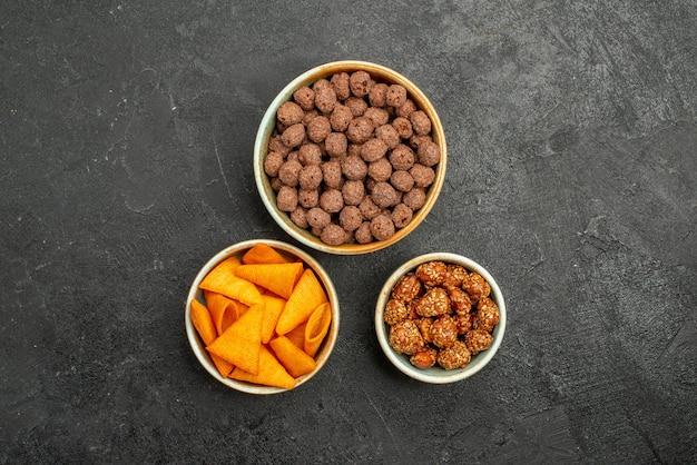Scaglie di cioccolato vista dall'alto con scaglie su noce snack di colore di sfondo grigio scuro