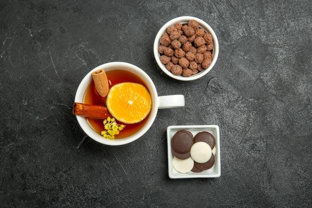 Vista dall'alto nocciole al cioccolato ciotole di cioccolato e nocciole una tazza di tè con cannella e limone sulla superficie scura