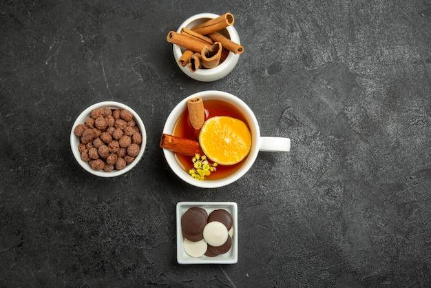 Vista dall'alto di nocciole al cioccolato ciotole di bastoncini di cannella cioccolato e nocciole e tazza di tè con cannella e limone sul lato sinistro del tavolo