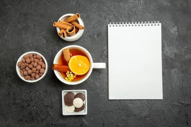 Quaderno bianco di nocciole al cioccolato con vista dall'alto e ciotole di bastoncini di cannella cioccolato e nocciole accanto alla tazza di tè con cannella e limone sul lato sinistro del tavolo
