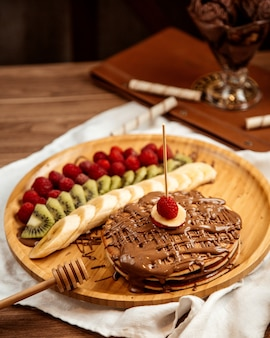 Top view chocolate pancakes with banana kiwi and strawberries on a tray