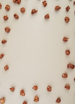 Vista dall'alto di popcorn al cioccolato su bianco con spazio di copia