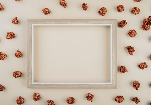 Vista dall'alto di popcorn al cioccolato con cornice sul centro su bianco con spazio di copia