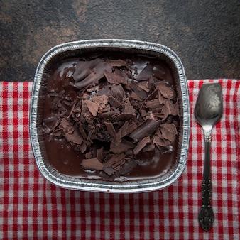 Вид сверху шоколадный пудинг с античной ложкой и тряпкой в фольгированной тарелке