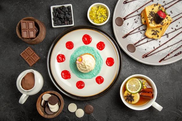Vista dall'alto cioccolato sul tavolo ciotole di erbe al cioccolato e una tazza di tè appetitoso al limone accanto alla torta con cioccolato e fragole e cupcake con crema