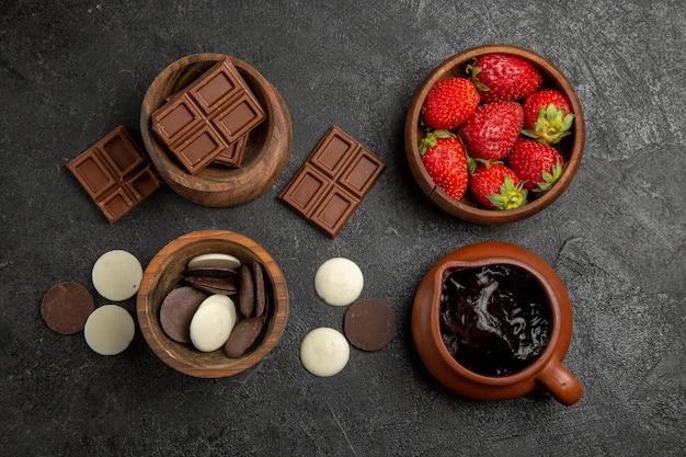 Vista dall'alto cioccolato sul tavolo ciotole marroni di fragole al cioccolato e salsa al cioccolato sulla superficie scura