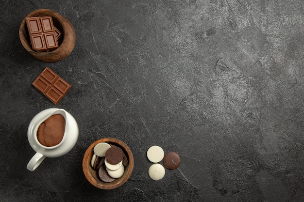 Top view chocolate on the table chocolate and chocolate cream in the wooden bowls on the black table