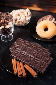 Vista dall'alto di tavolette di cioccolato, ciambelle, zucchero di canna con arachidi al cioccolato e chicchi di caffè su fondo di legno vintage scuro