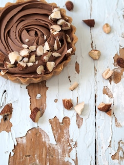 Top view of chocolate tarts served almond nuts on shabby white wooden background