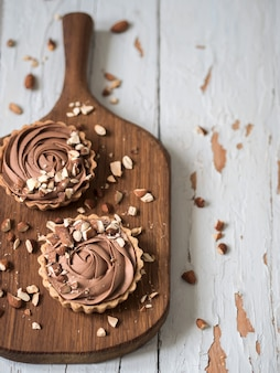 Top view of chocolate tarts served with almond nuts on shabby white wooden surface