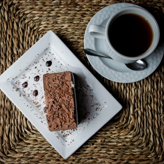 Top view chocolate tiramisu with cup of tea and white plate and spoon in serving napkins