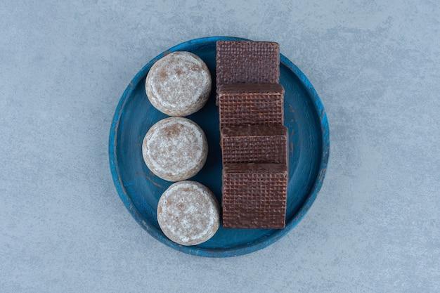 Vista dall'alto di wafer al cioccolato con biscotti fatti in casa su piatto di legno blu.