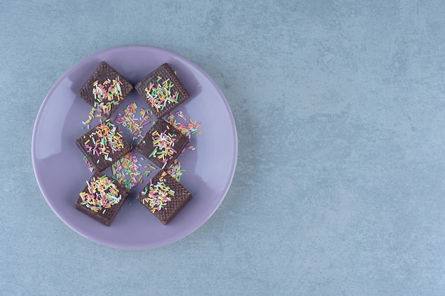 Vista dall'alto di wafer al cioccolato con cospargere sul piatto viola.