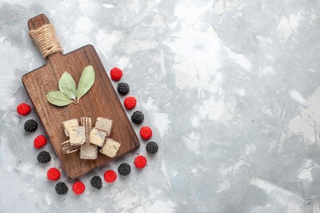 Vista dall'alto di cialde al cioccolato con confettura di frutti di bosco sulla scrivania leggera, cialda di caramelle biscotto