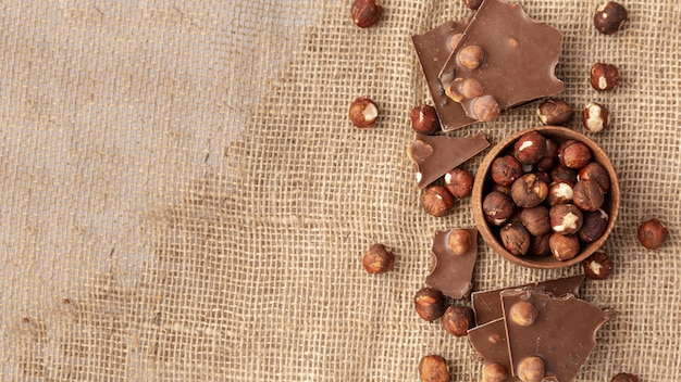 Top view of chocolate with hazelnuts on burlap and copy space