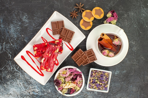 Vista dall'alto di cioccolatini sul piatto bianco con tisane e fiori secchi e biscotti su fondo grigio