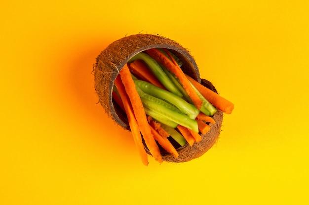 Вид сверху нарезанная морковь с огурцом в кокосе