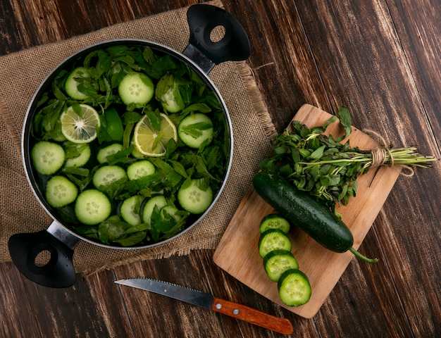 Top view of chopped cucumbers with mint in a pan with a cutting board and knife on a wooden surface