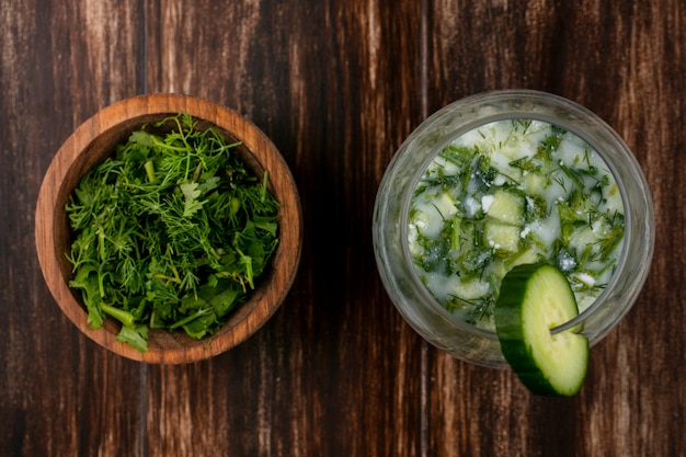 Top view of chopped greens with okroshka and cucumber on a wooden surface